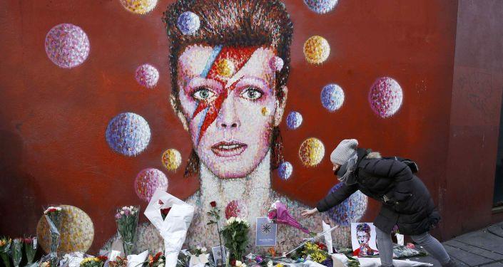 Fanka Davida Bowie składa kwiaty pod portretem-graffiti artysty w Londynie
