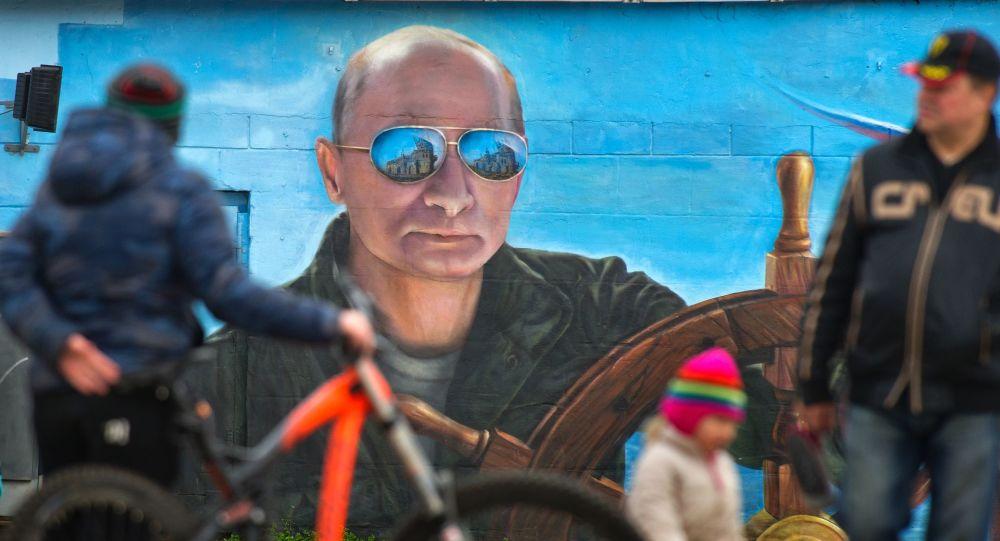 Przechodnie przy portrecie prezydenta Rosji Władimira Putina na ścianie budynku w Jałcie