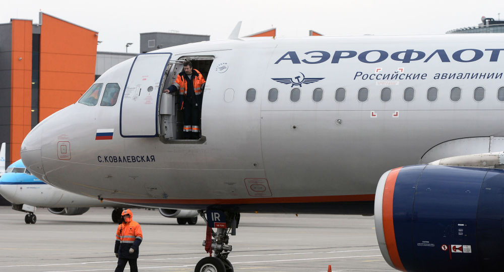 Pracownicy lądowych służb technicznych w pobliżu samolotu Airbus A320 linii lotniczych Aerofłot na międzynarodowym lotnisku Szeremietiewo