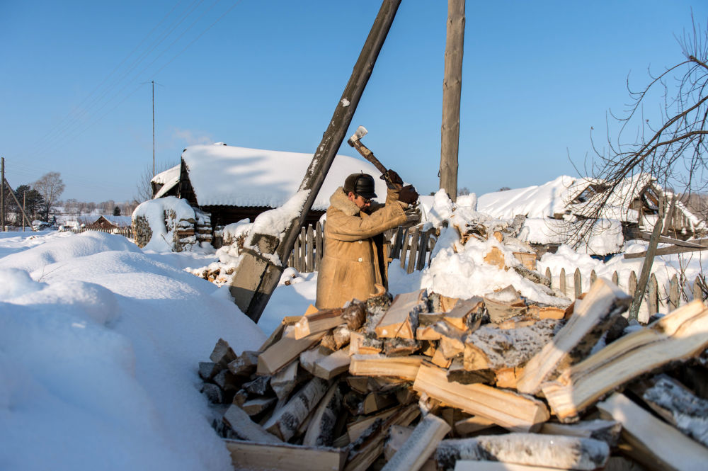 Mężczyzna rąbie drewno w miejscowości Maszanka dzielnicyTarskiej