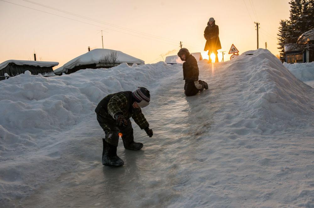 Dzieci jeżdżą z górki na wsi Jermakowka dzielnicy Tarskiej