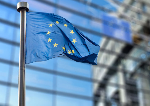 Flaga Unii Europejskiej na tle budynku Parlamentu Europejskiego w Brukseli