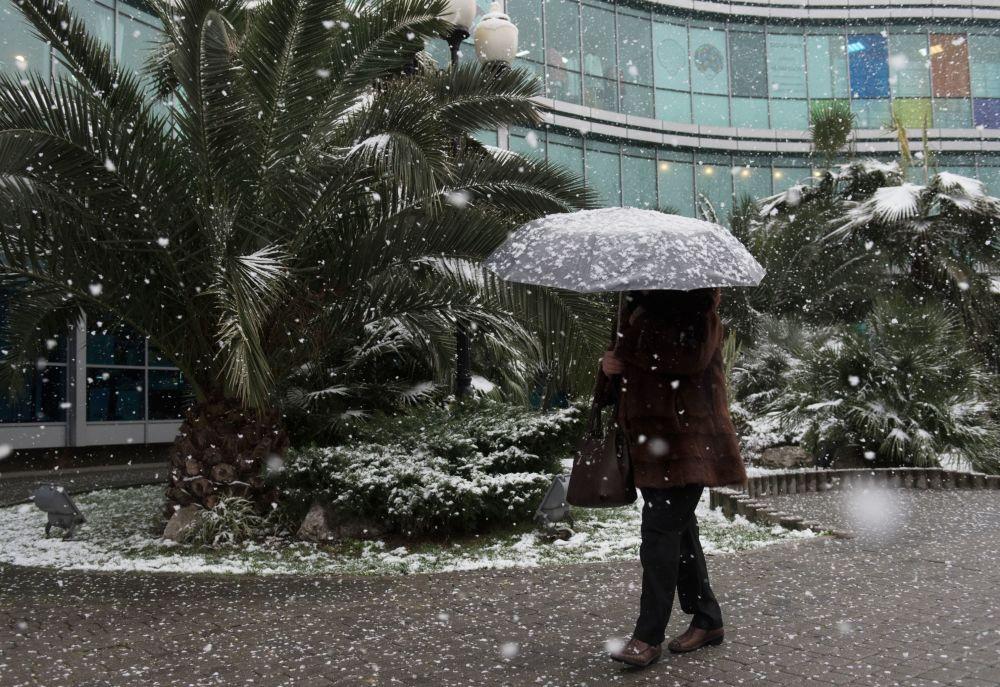 Kobieta na ulicy w Soczi podczas opadów śniegu