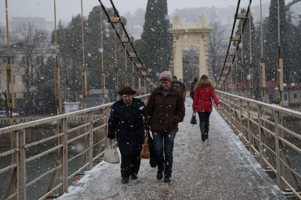Przechodnie w Soczi podczas opadów śniegu
