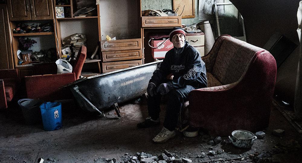 Mężczyzna w zniszczonym mieszkaniu w Doniecku