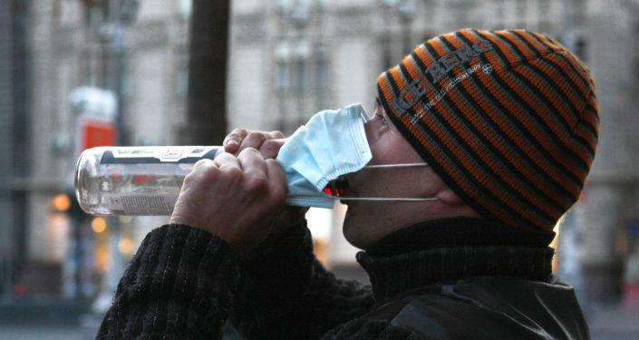 Mieszkaniec Kijowa w masce ochronnej pije wódkę