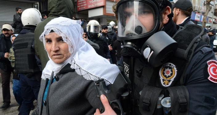 Turecki policjant zatrzymuje kobietę w czasie rozpędzenia demonstrantów w mieście Çınar