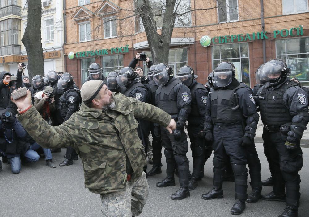 Ukraiński nacjonalista rzuca kamień w stronę jednego z rosyjskich banków w Kijowie