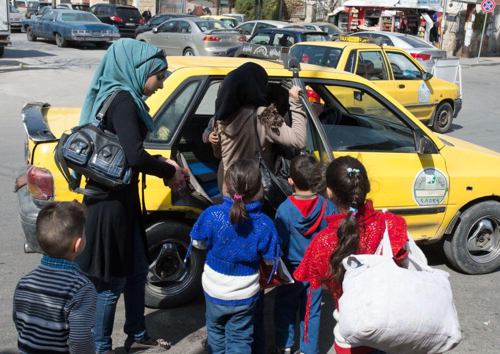 Kobiety z dziećmi wsiadają do taksówki na ulicy Damaszku