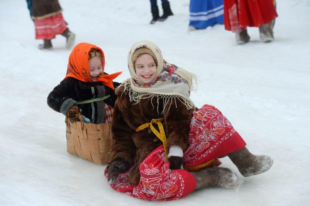 Dziewczynki zjeżdżają z górki w pierwszy dzień Maslenicy w obwodzie archangielskim w Rosji.
