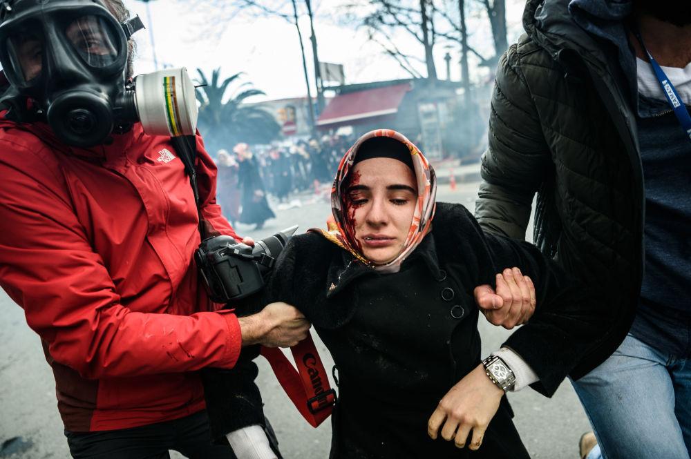 Dziennikarze pomagają kobiecie po zamieszkach w Stambule