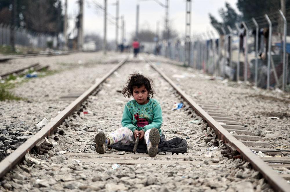 Dziewczynka bawi się na kolejach na granicy grecko-macedońskiej