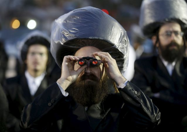Ultraortodoksyjny Żyd z lornetką na tradycyjnym żydowskim weselu w Netanji