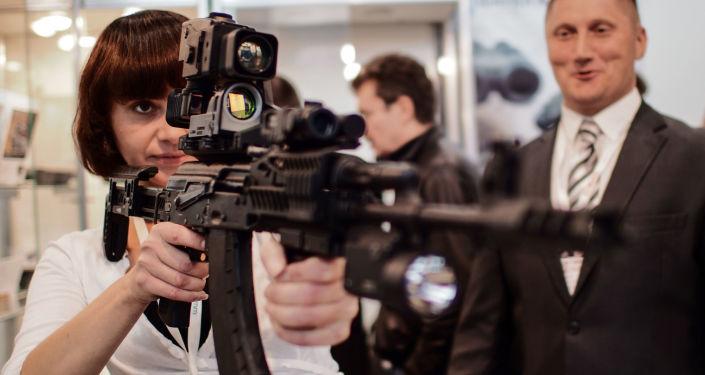 Dziewczyna trzyma karabin Kałasznikowa AK-103