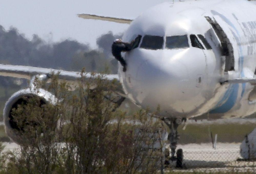 Mężczyzna wychodzi przez rozbite okno samolotu linii Egyptair na lotnisku w Larnace