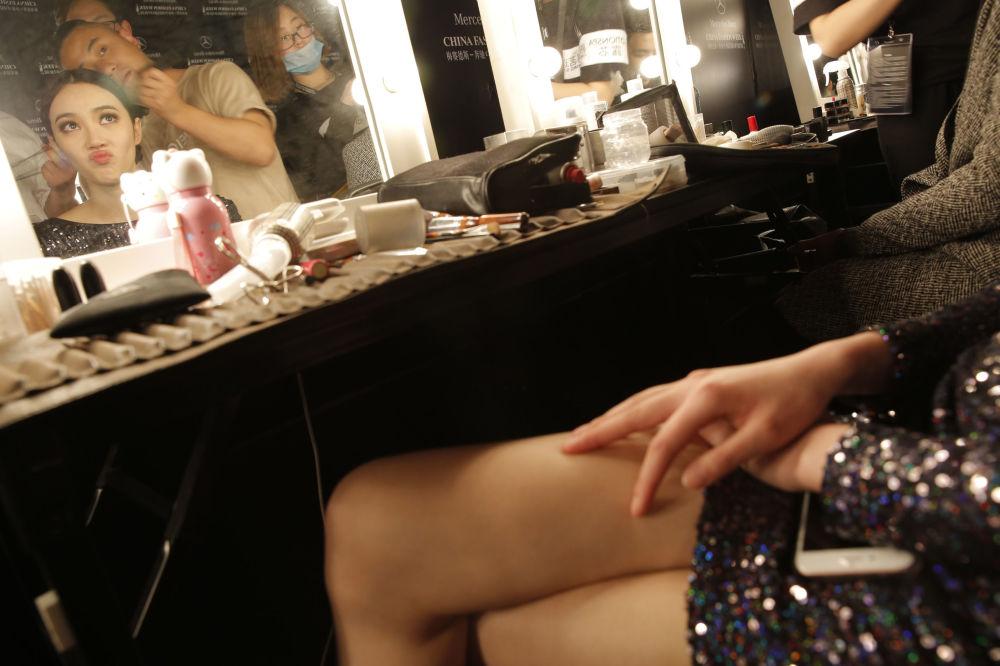 Modelka w czasie charakteryzacji na pokazie mody China Fashion Week w Pekinie