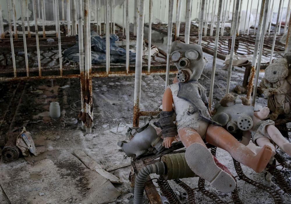 Dziecięca lalka w masce przeciwgazowej w ruinach Prypeci