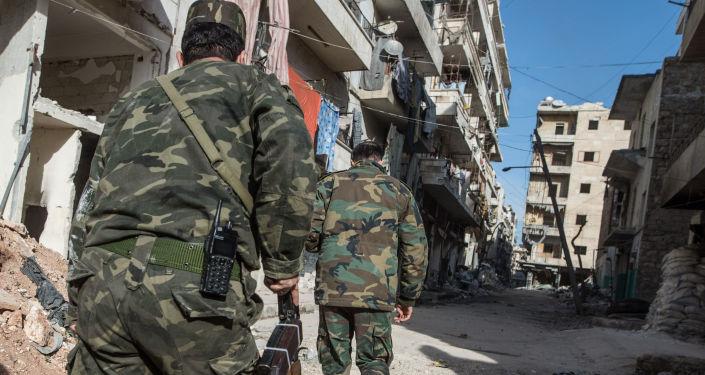 Wojskowi syryjskiej armii w dzielnicy mieszkalnej w mieście Aleppo