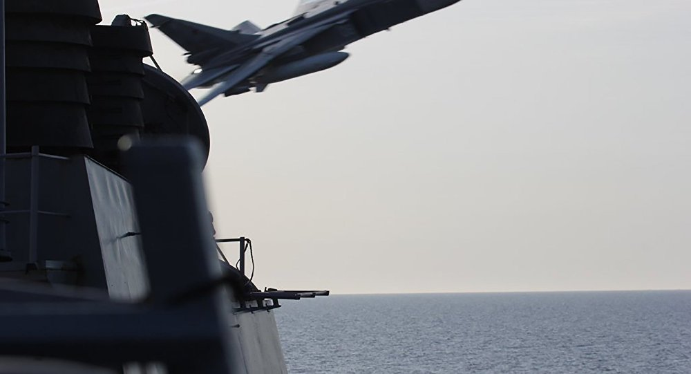 An undated US Navy picture shows what appears to be a Russian Sukhoi SU-24 attack aircraft making a very low pass close to the U.S. guided missile destroyer USS Donald Cook in the Baltic Sea.