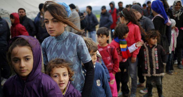 Uchodźcy stoją w kolejce po herbatę w obozie w greckiej miejscowości Idomeni