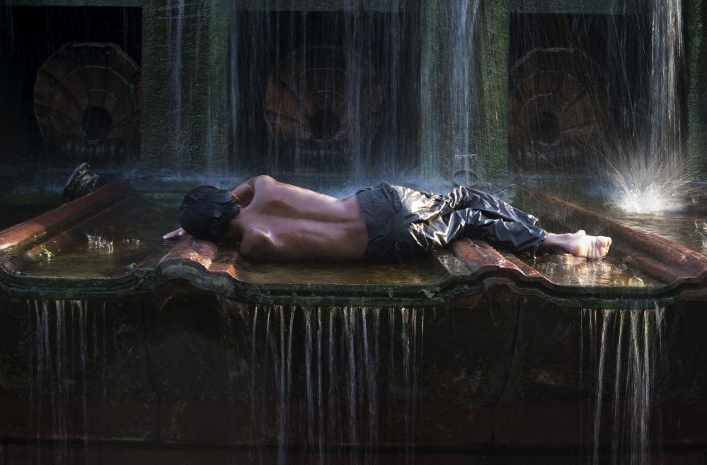Dziesięcioletni chłopiec włóczęga przy fontannie w gorący dzień (New Delhi, Indie).