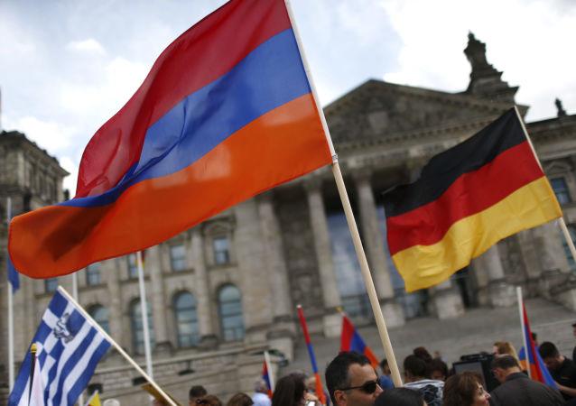 Ormiański i niemiecki flagi na tle Reichstagu w Berlinie