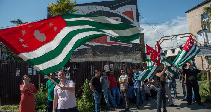 Mieszkańcy Abchazji z flagą narodową na ulicach w Suchum