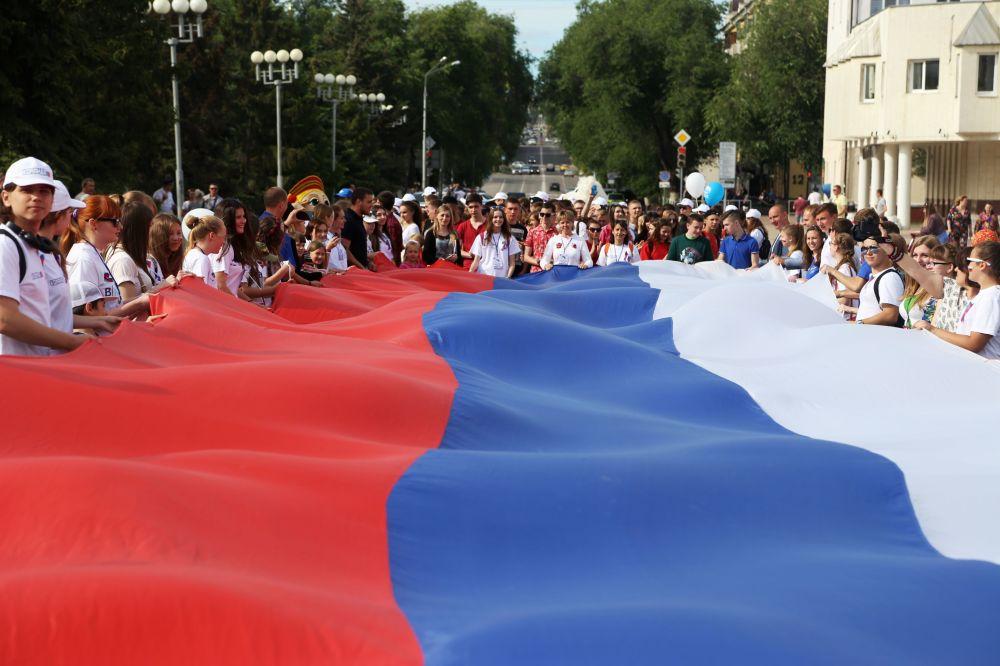 Wolontariusze z flagą Rosji podczas obchodów Dnia Rosji w Biełgorodzie