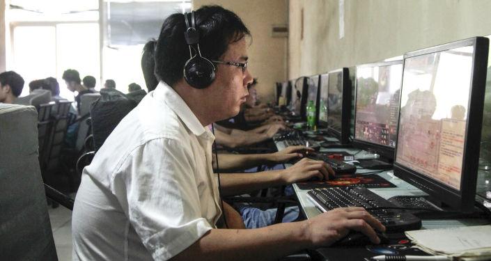 Ludzie za monitorami w kawiarence internetowej w Chinach