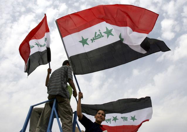Chłopcy trzymają irackie flagi