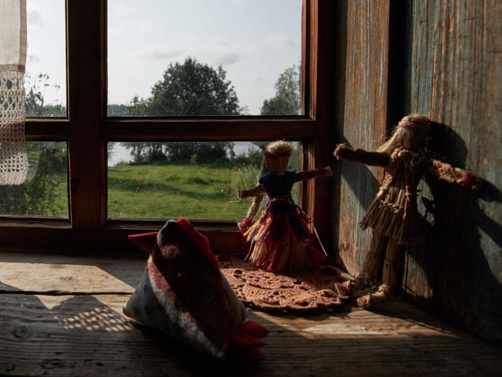 Lalki na oknie w izbie we wsi Mandrogi w obwodzie leningradzkim.
