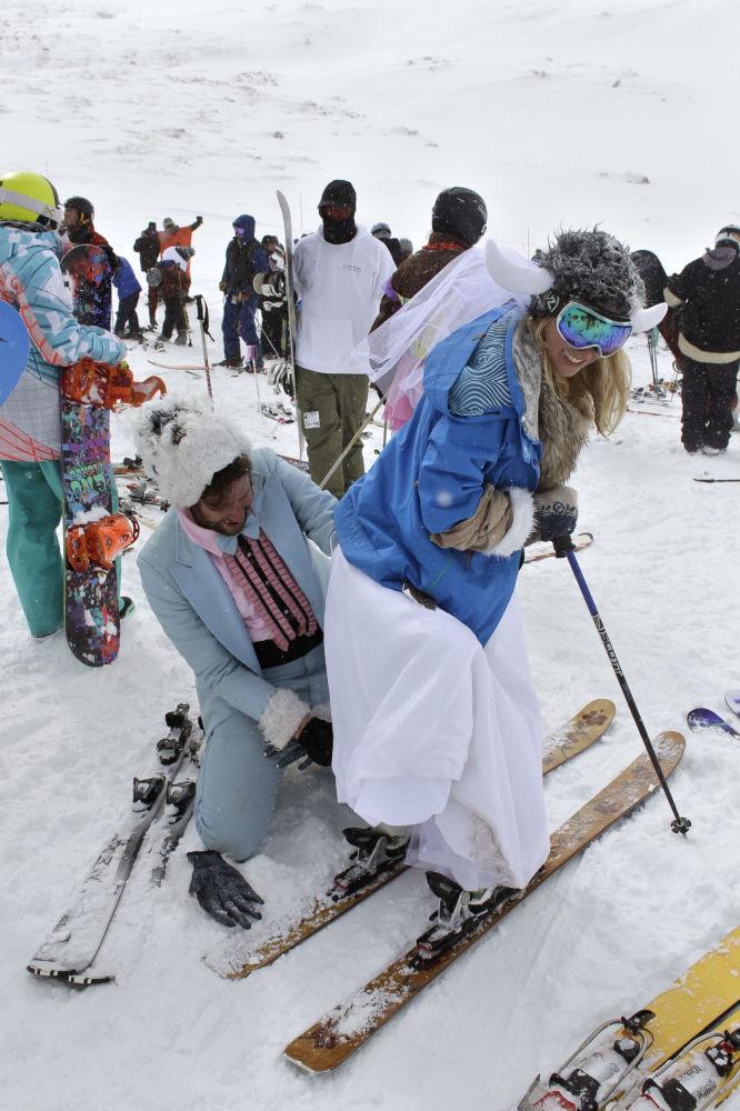 Para młoda w trakcie ślubu zbiorowego na nartach w Colorado.