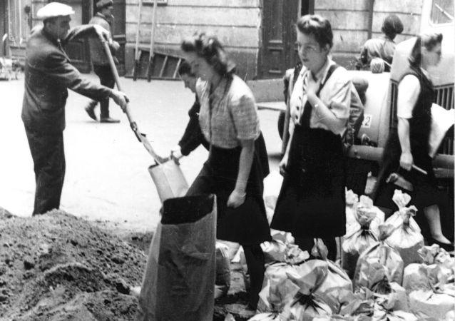 Mieszkańcy Warszawy napełniają worki z piaskiem w czasie Powstania Warszawskiego, 1944.
