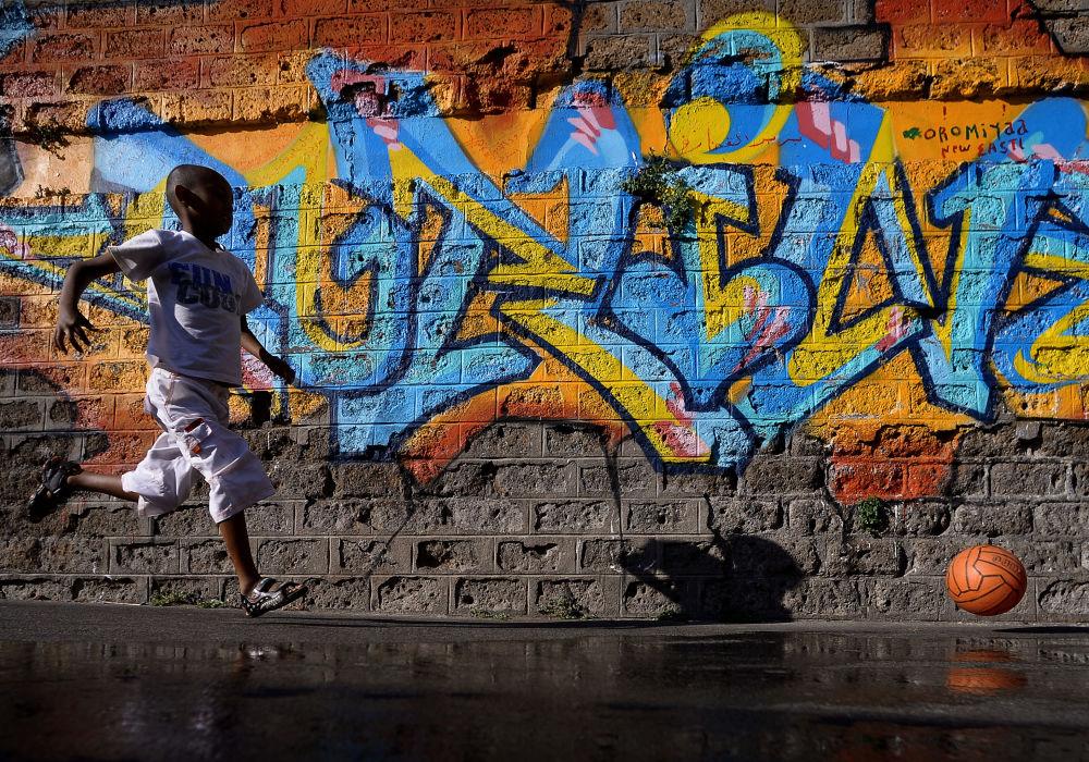 Dziecko uchodźców biegnie za piłką obok zamkniętego ośrodka dla migrantów w Rzymie