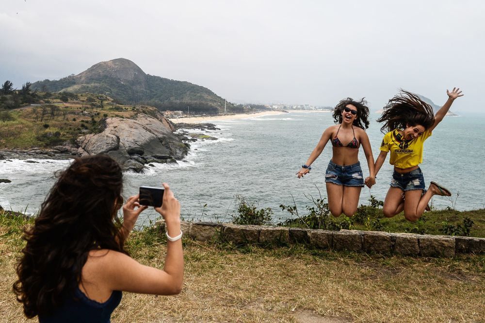 Kibicka fotografuje się czekając na sportsmenki podczas zawodów kolarskich kobiet na XXXI letnich Igrzyskach Olimpijskich