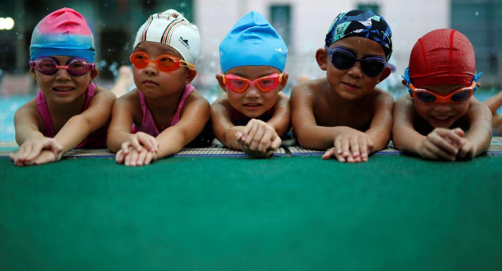 Dzieci na zajęciach na basenie w szkole pływania