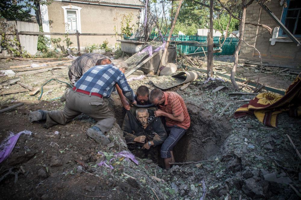 Miejscowi mieszkańcy wyciągają z ukrycia ciało zabitego w wyniku ostrzału miejscowści Aleksandrowka w obwodzie donieckim