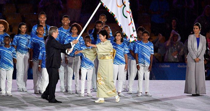 Przewodniczący MKOl Thomas Bach przekazuje flagę igrzysk burmistrzyni Tokio Yuriko Koike podczas ceremonii zamknięcia igrzysk olimpijskich w Rio