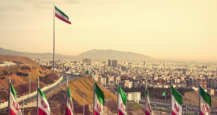 Flagi Iranu, w tle Teheran