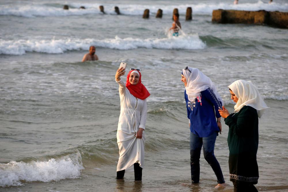 Dziewczyny w hidżabach robią selfie na jednej z plaż Tel Awiwu