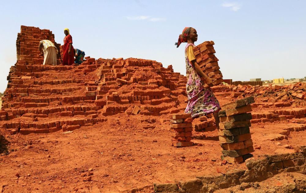 Kobieta nosi cegły w obozie dla przesiedleńców w El-Faszir, Sudan
