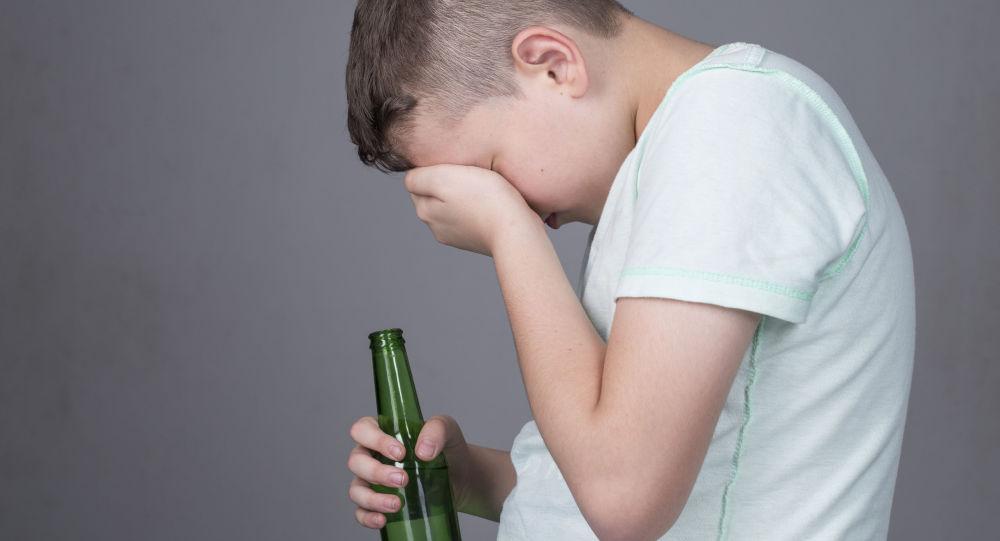 Nastolatek z butelką alkocholu