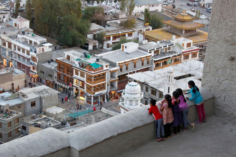 Dzieci patrzą w dół z dachu pałacu w mieście Leh, Himalaje