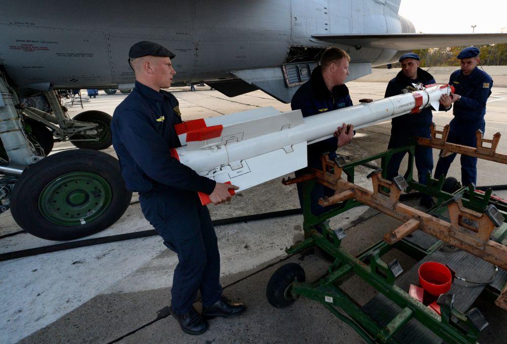 """Mechanicy mocują rakietę klasy """"powietrze-powietrze"""" pod skrzydłem myśliwca MiG-31 podczas lotno-taktycznych ćwiczeń pułku myśliwskiego na wojskowym lotnisku """"Centralnaja Ugłowaja"""" w Kraju Nadmorskim"""