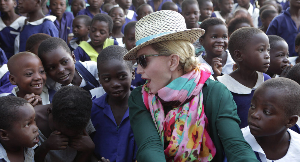 U.S singer Madonna chats with children in Kasungu, about 150 kilometers north of the capital Lilongwe, Sunday, Nov. 30, 2014