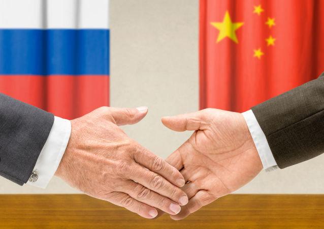 Dłonie na tle flag Rosji i Chin