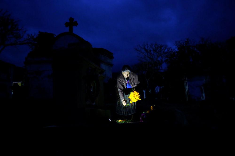 Kobieta z kwiatami na cmentarzu w Dniu Wszystkich Świętych w Gwatemali