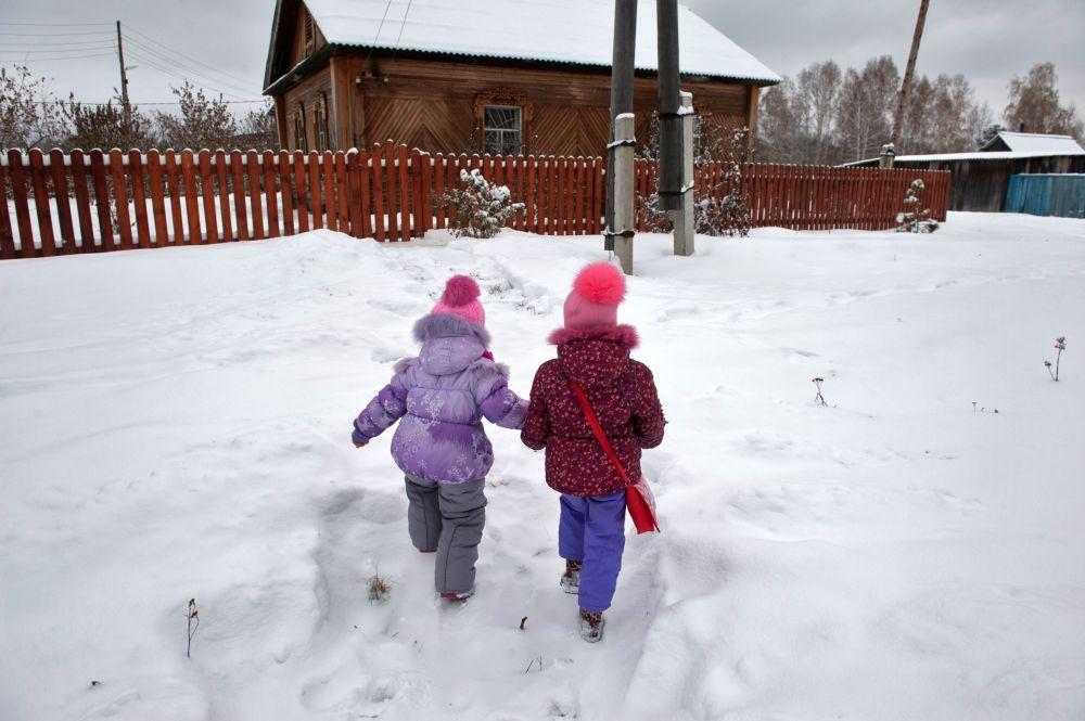 Dzieci idą po ścieżce w śniegu do domu