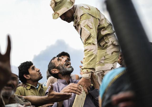 Irakijczycy czekają na rozdanie produktów żywnościowych w obozie dla uchodźców w Mosulu