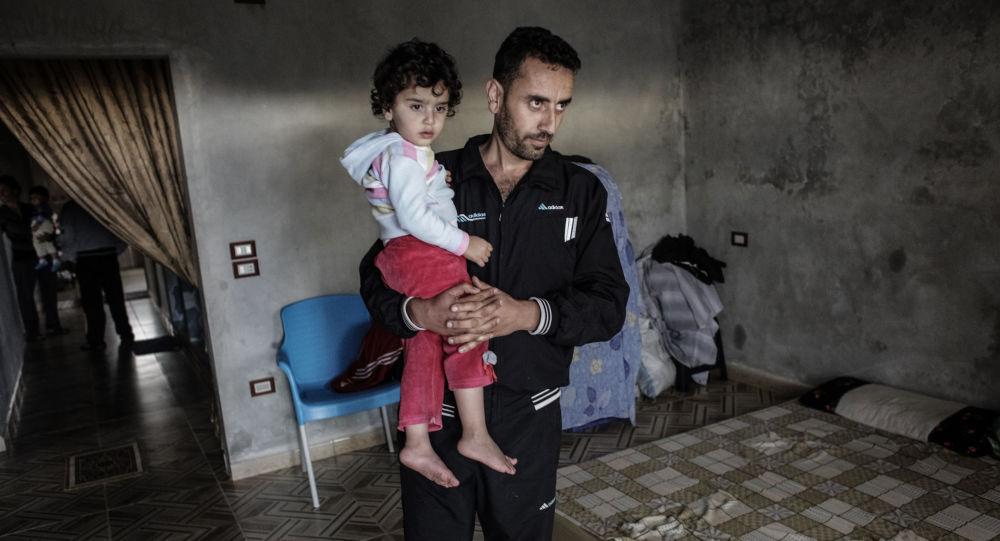 Mężczyzna z dzieckiem w domu, w którym przez kilka dni nocowali terroryści. Wioska Udin w prowincji Latakia